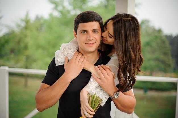 笑顔の彼氏を後ろから抱いて幸せで美しい女性