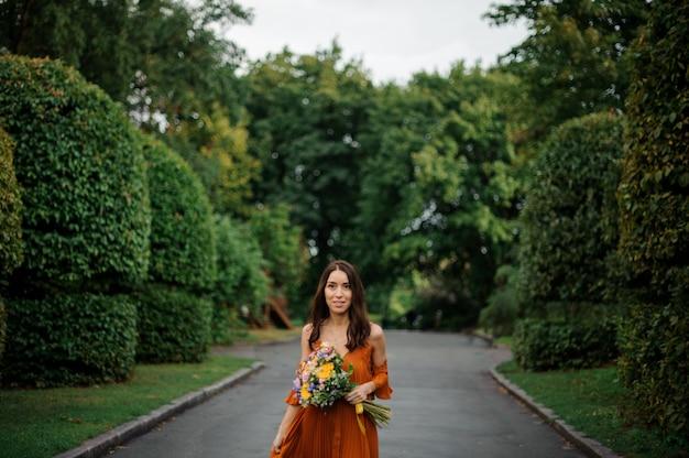 オレンジ色の長いドレスの若くて美しい女性