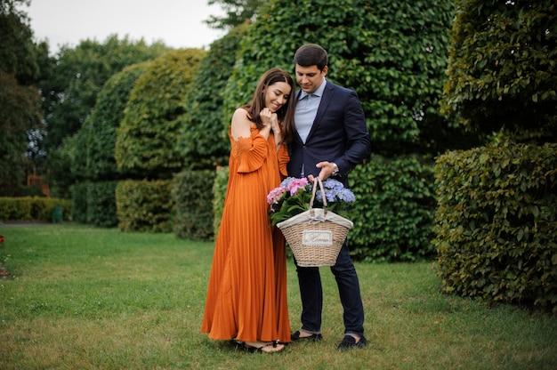 花でいっぱいの大きな枝編み細工品バスケットを持つ美しく、スタイリッシュなカップル