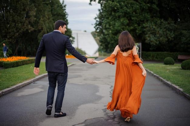 愛のカップルが手を繋いでいると道を歩いての背面図