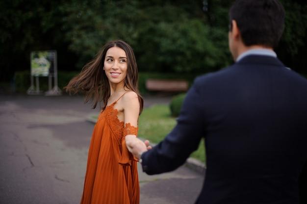 男の背面図は美しい女性の手を握ってスーツです。