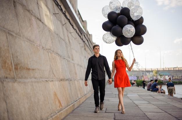 若くて美しいカップルが遊歩道に沿って歩く
