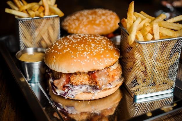 おいしいハンバーガーとフライドポテト、鉄の皿にソース添え