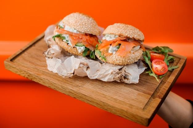 サーモン、ソース、キュウリ、トマト、ルッコラの冷たいハンバーガーを木製プレートで提供