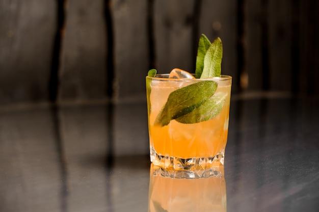 サルビアの葉で飾られた氷とオレンジ色のアルコール飲料の分離ガラス