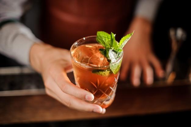 バーテンダーは、アルコール飲料とミントのショットグラスを保持しています。