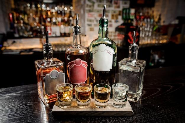 Бутылки и стаканы с алкогольными напитками на барной стойке