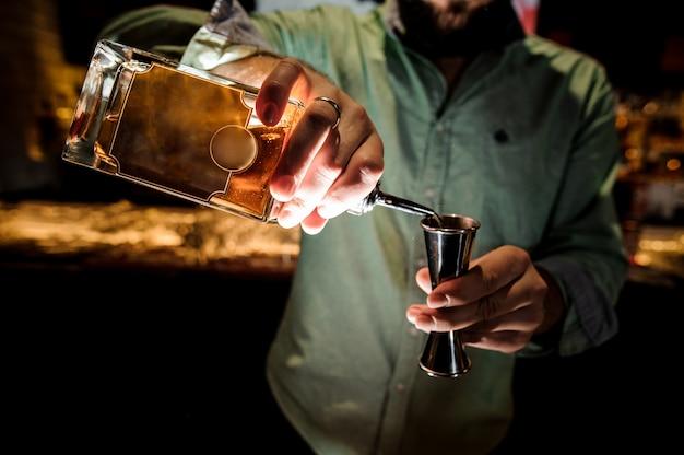 Бармен наливает сироп для приготовления коктейля