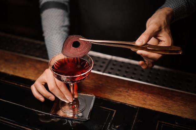 赤い装飾が施されたアルコール飲料を作るバーテンダー