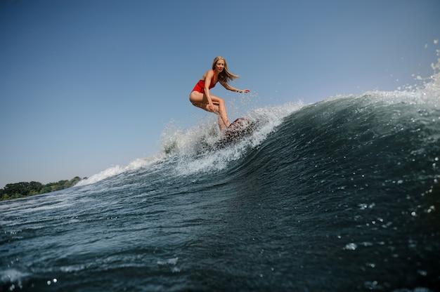 緩い髪を持つ女性は海でサーフィンします。