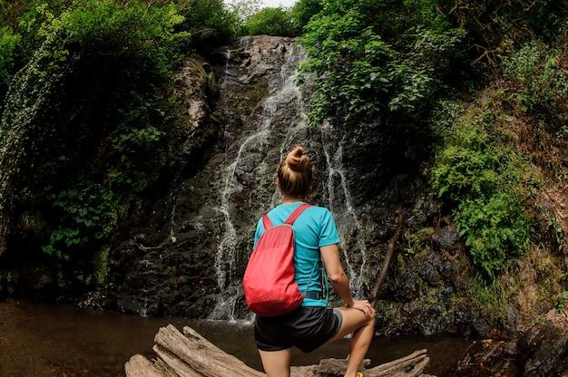 森の美しい滝を見て思わぬ障害の上に立っている魚眼写真の女の子