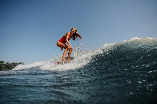 長い髪を持つ女性は海でサーフィンします。