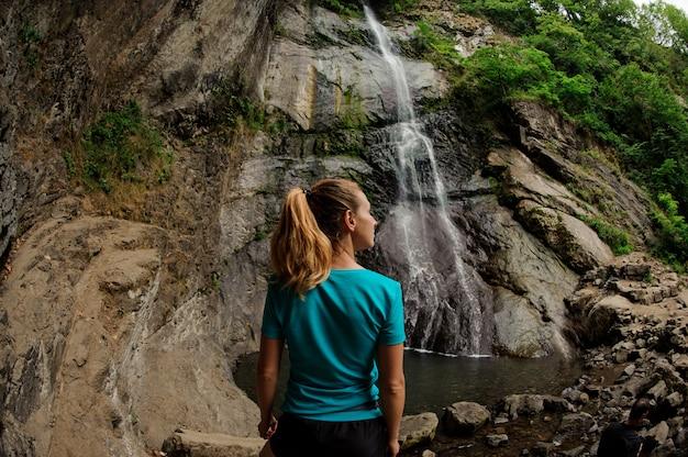 立っていると、森の中の美しい滝を見て魚眼写真背面ビューの女の子