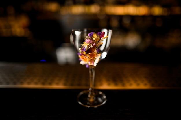 Пустой стакан, украшенный различными разноцветными цветами, стоящими в баре