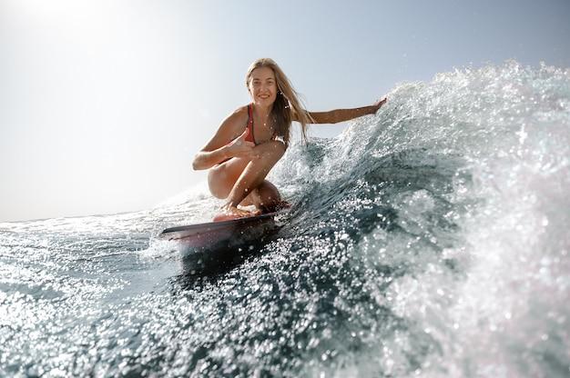 水着サーフィンの女性のショットを閉じる