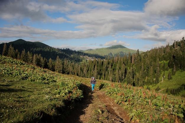 ハイキングのバックパックと木の覆われた丘の背景に棒で未舗装の道路の上を歩く男