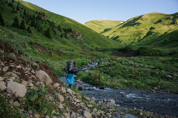 バックパックとストリームに沿ってスティックをハイキングで山の川の近くを歩く男