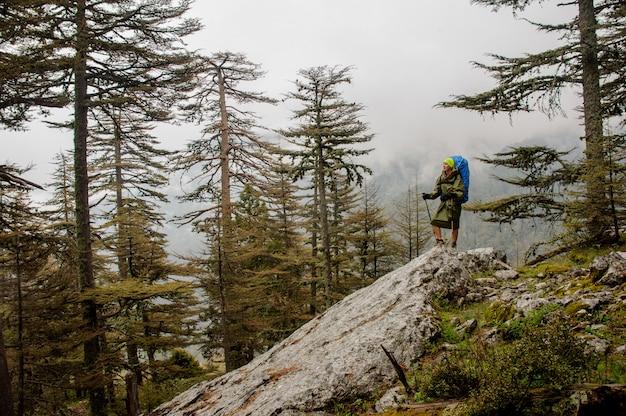 バックパックとスティックをハイキングで岩の上に立っているレインコートの女の子