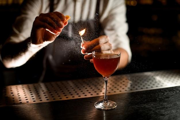 バーテンダーがグラスにカクテルを添えて、レモンジュースとマッチを燃やす