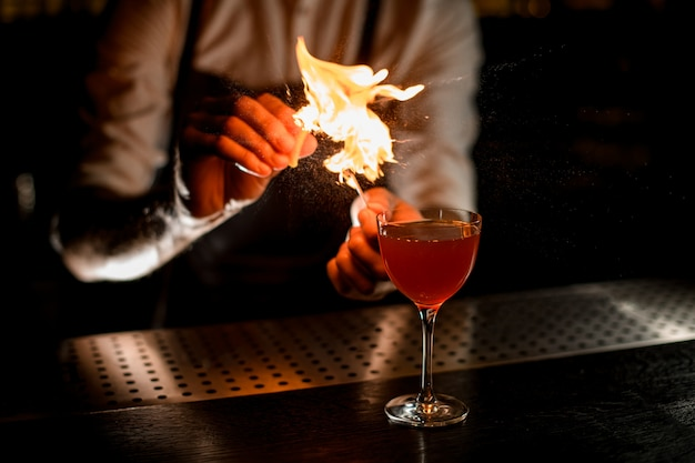 バーテンダーが燃えているマッチに吹きかけるグラスでカクテルを提供