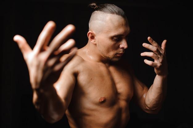 スタイリッシュな散髪で裸の日焼けした筋肉のセクシーな男