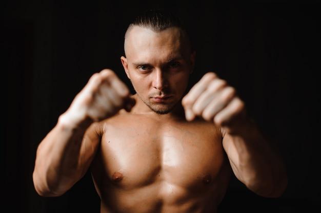 彼の拳を食いしばって筋肉質で熱い男