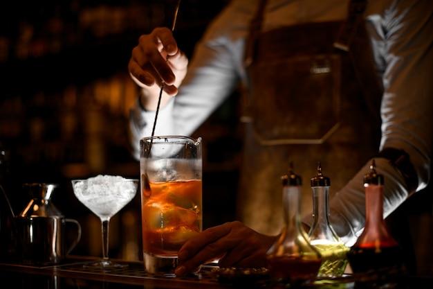 Бармен размешивает алкогольный коктейль с ложкой