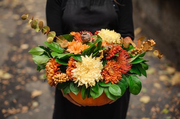 女性の手に花の美しい花束とカボチャ