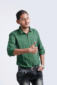 親指を現して若いインドの大学生。