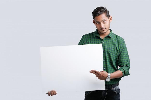 Молодой индийский мужчина показывает пустой петь доска на белом фоне