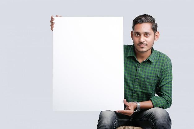 白い背景の上に空白の歌うボードを示す若いインド人