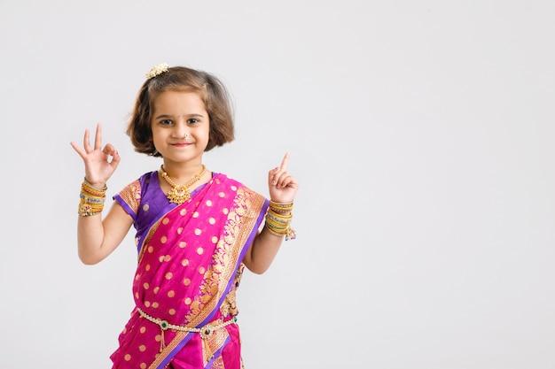 Милая маленькая индийская / азиатская девушка показывая направление