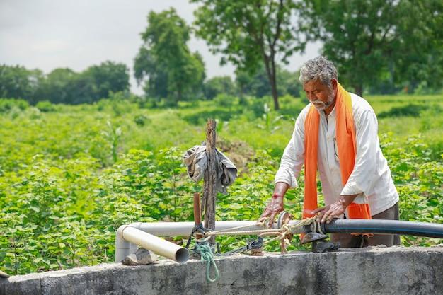 Молодой индийский фермер работает на поле