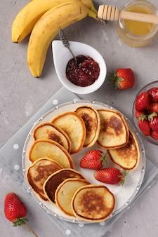 自家製の朝食。ベリージャム、蜂蜜、バナナ、コンクリート背景の灰色のナプキンにイチゴのパンケーキ