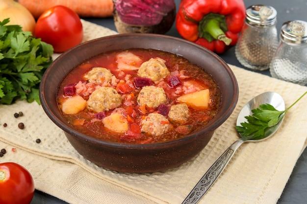 暗いボウルにミートボールと野菜のスープ