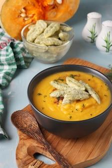 Тыквенный крем-суп с сырными кнедликами в темной миске на голубом фоне, вертикальный формат, крупным планом