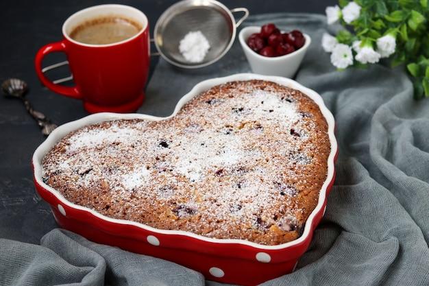 Овсяный пирог с вишней посыпанный сахарной пудрой в керамической форме в форме сердца