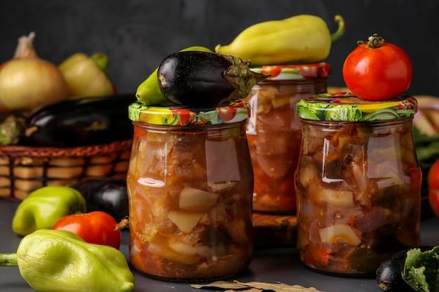 Овощной салат с баклажанами, луком, перцем и помидорами в банках на темном