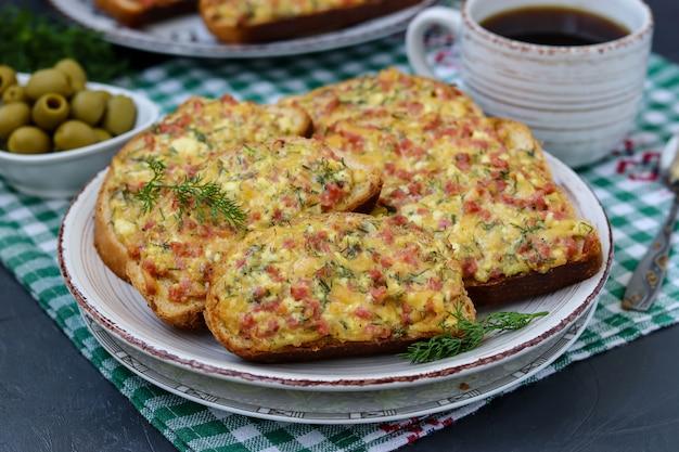 Домашние горячие бутерброды с сыром и колбасой в тарелке на клетчатой скатерти,