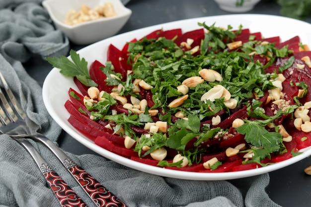 Здоровый салат из свеклы с арахисом и петрушкой на белой тарелке