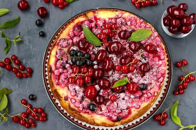 Летний творожный пирог с ягодами расположен на темном фоне