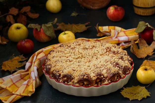 Пирог с яблоками расположен в керамическом виде, яблоки разбросаны по столу