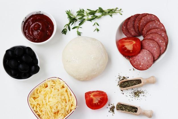 ピザの材料:生地、ソーセージ、トマト、オリーブ、トマトソース、チーズ、バジル、プロヴァンスのハーブ