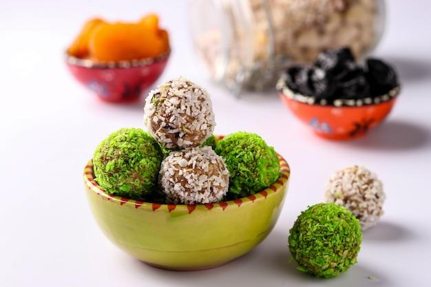 Энергетические шарики из орехов, овсянки и сухофруктов, посыпанные зелеными и белыми кокосовыми хлопьями на тарелке