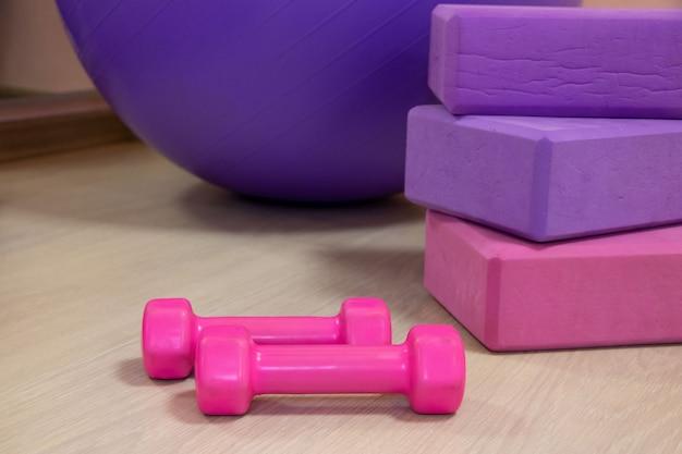 Фитнес-инструменты - мяч, розовые и фиолетовые кубики и гантели, спортивная концепция