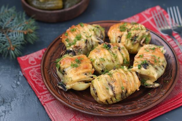 Запеченный картофель-гармошка с грибами и сыром, расположенный в тарелке на темном