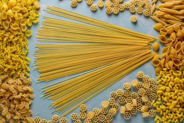 Ассорти итальянских макаронных изделий: пенне ригате, ротель, кончигли, каватаппу, фузилли, целлентани, спагетти, горизонтальная ориентация, вид сверху