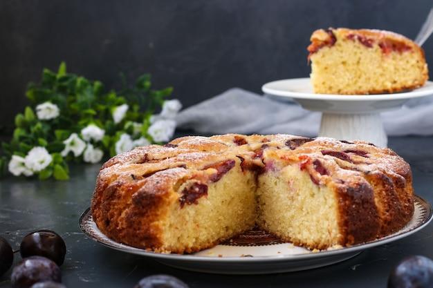 Сливовый пирог с вырезанным куском расположен на тарелке
