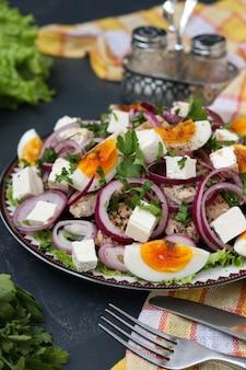 チキン、ビート、ゆで卵、赤玉ねぎ、フェタチーズ入りのオーガニックレタスのヘルシーサラダ