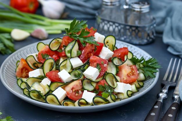Полезный салат с цуккини, помидорами и сыром фета, заправленный оливковым маслом в тарелке на темной горизонтальной ориентации